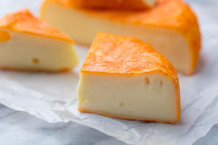 Cheese with washed orange rind. French or German. Marble table background