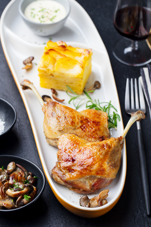 Duck legs confit with potato gratin and mushroom. Restaurant serving. Copy space. Top view. Stok Fotoğraf - 107516974