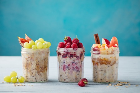 Overnight oats, bircher muesli with fresh berries and fruits in a glass jars on wooden table background. Copy space Stock fotó