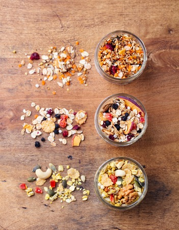 Assortment of granola, muesli in glass jars. Organic oats with apples, berries and nuts. Top view