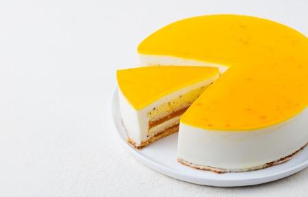 Torta al frutto della passione, dessert mousse su un piatto bianco. Copia spazio