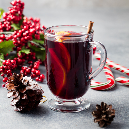 Mulled red wine with spices, orange slices. New year and Christmas background. Imagens
