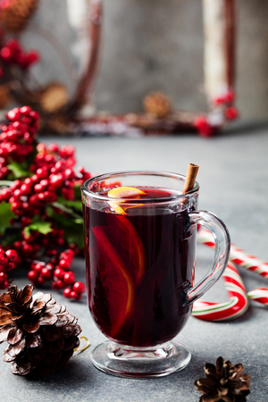 Mulled red wine with spices, orange slices on grey table. New year and Christmas background. Imagens