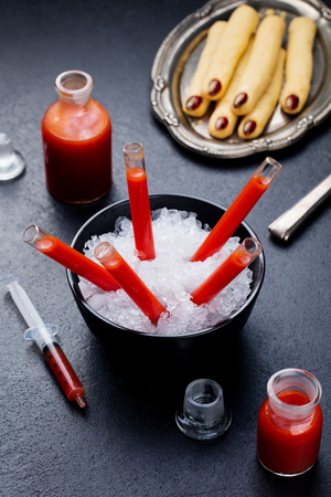 Bloody Mary cocktail in glass tubes with Witchs fingers cookies for Halloween party celebration. Slate background.