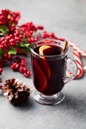 Mulled red wine with spices, orange slices on grey stone new year and Christmas background.
