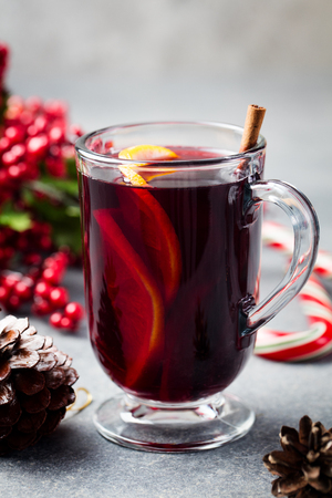Mulled red wine with spices, orange slices. New year and Christmas background. Copy space. Imagens