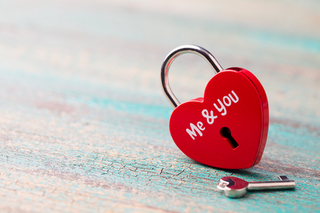 Heart shaped padlock with a key on blue wooden background. Copy space. Stock Photo - 109096204