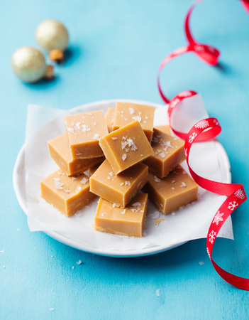 Fresh caramel fudge candies on a plate with Christmas red ribbon on blue background.