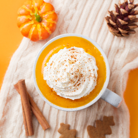 Pumpkin latte with spices. Boozy cocktail with whipped cream on top on knitted scarf. Orange background.