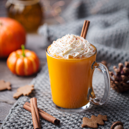 Pumpkin latte with spices and whipped cream. Grey background. Close up.