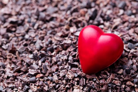 Heart shaped chocolate candy on crushed cocoa nibs. Close up. Copy space. Stok Fotoğraf