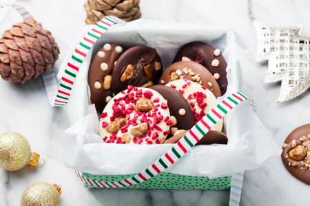Chocolate mediants, bites, candies in a gift box for Christmas and New Year celebration. Marble background.