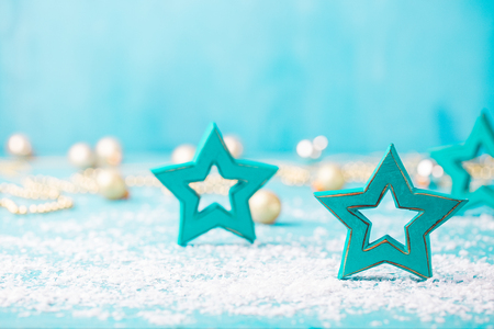 Christmas, New Year blue background with wooden star and snow decorations. Copy space.