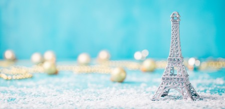 Christmas, New Year blue background with snow and Eiffel tower ornament. Copy space.