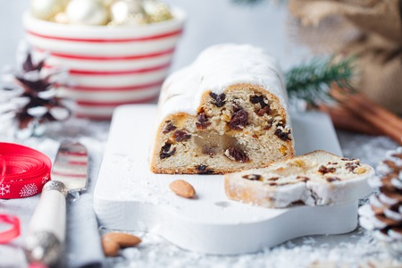 Christmas stollen cake with icing sugar, marzipan and raisins. Traditional Dresdner christ pastry. Close up.