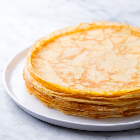 Crepes, thin pancakes, blini on a white plate. Marble background. Close up