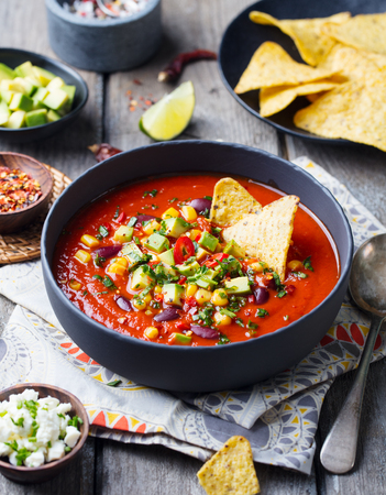 Mexican tomato, bean, bell pepper soup in black bowl with nachos chips. Wooden background Stock Photo