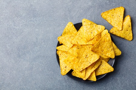 Nachos chips in bowl. Grey stone background. Top view. Copy space Stock Photo