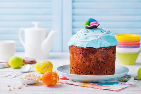 Easter cake with colorful eggs. White and blue wooden background. Copy space. Stock Photo