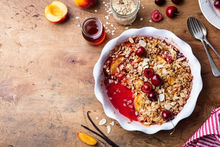 Peach and berry crumble in a baking dish. Top view. Copy space Stock Photo