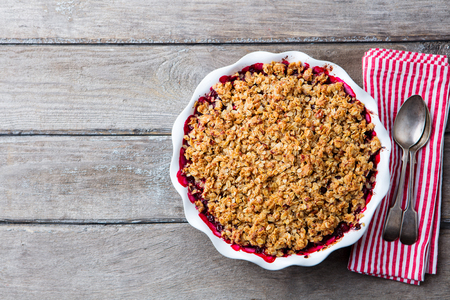 Berry crumble in white baking dish on grey wooden background. Top view. Copy space Stock Photo