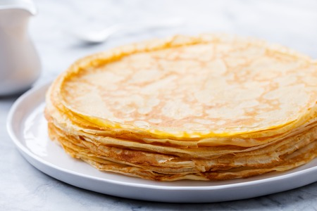 Crepes, thin pancakes with honey on a white plate. Close up