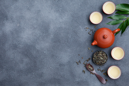 Green tea in tea pot and chawan bowls, cups on slate background. Top view. Copy space