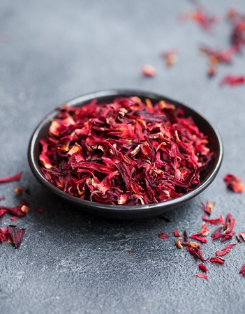 Hibiscus tea in black bowl. Slate background. Copy space