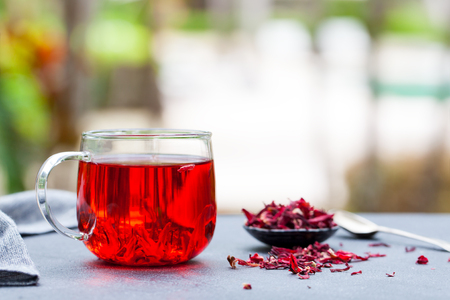 Hibiscus tea in glass cup. Grey background. Copy space. Outdoor background. Stock Photo