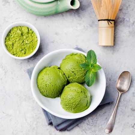 Łyżka do lodów matcha zielonej herbaty w białej misce. Szary kamień tło. Widok z góry.