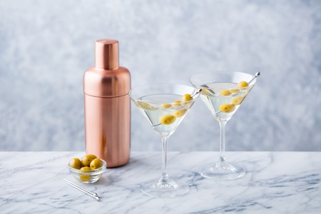 Martini cocktail with green olives, shaker on marble table background.