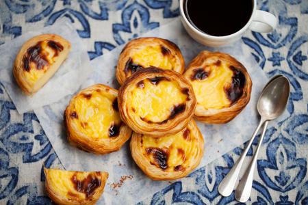 Tarta jajeczna, tradycyjny portugalski deser, pastel de nata z kawą. Niebieskie tło.