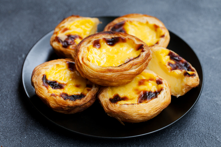 Egg tart, traditional Portuguese dessert, pastel de nata on a plate. Grey stone background.
