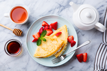 Crepes, thin pancakes with cream cheese, ricotta and fresh strawberries. Marble background. Top view. Imagens