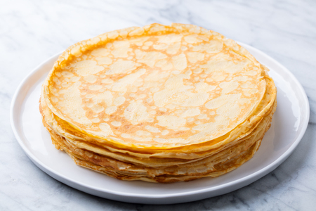 Crepes, thin pancakes with honey on a white plate. Marble background. Close up.