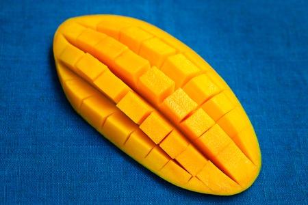 Fresh mango organic product on blue textile background. Close up. Imagens