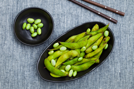 Fresh edamame green beans in black bowl. Grey background. Top view. Copy space.