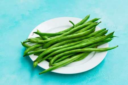 Green beans on white plate. Blue background. Close up.