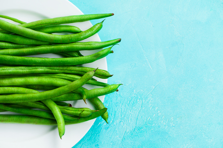 Green beans on white plate. Blue background. Copy space. Top view. Stock Photo