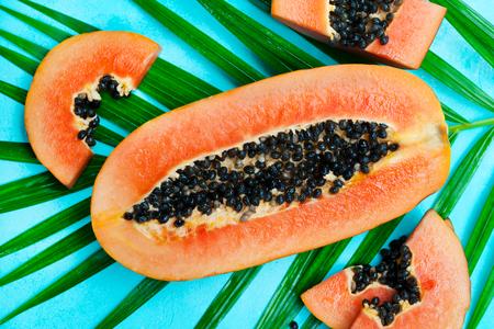 Fresh papaya fruit on palm leaf. Grey stone background. Top view. Stock Photo