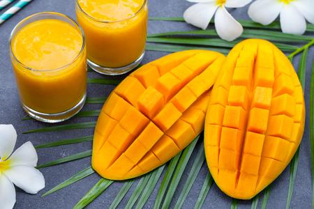 Fresh tropical fruit smoothie mango juice and fresh mango on grey background.