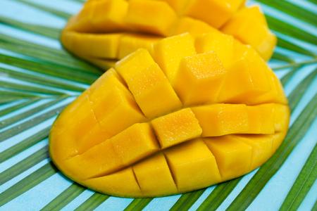 Fresh mango organic product on a palm leaf. Blue background. Close up.