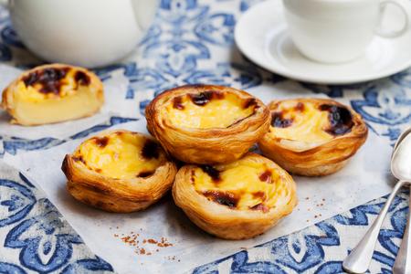 Eiertaart, traditioneel Portugees dessert, pastel de nata op een perkamentpapier. Blauwe achtergrond. Stockfoto