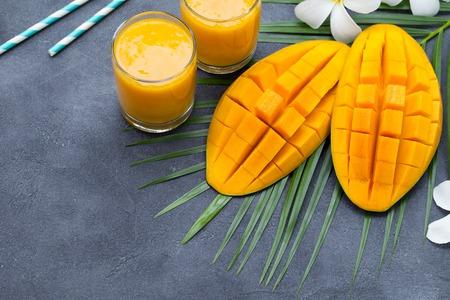 Fresh tropical fruit smoothie mango juice and fresh mango on grey background. Copy space. Imagens
