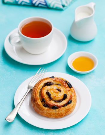 Fresh danish pastry with raisins and a cup of tea on blue table background.