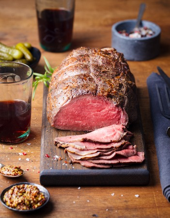 Roast beef on cutting board. Wooden background. Banque d'images - 122319185