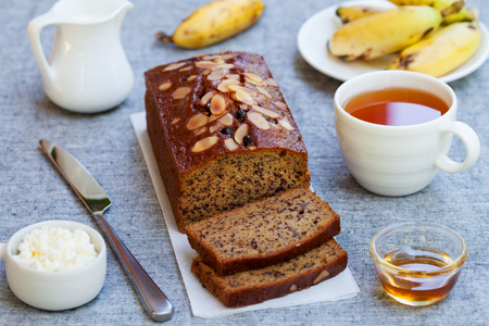 Banana cake, loaf bread with chocolate and cup of tea on grey textile background.