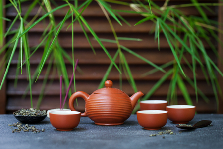 Green tea in tea pot and chawan bowls, cups on slate background. Copy space. Stockfoto