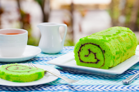 Green roll cake with a cup of tea. Summer outdoor background. Copy space.