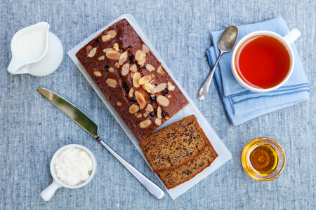 Banana, carrot, apple cake, loaf with chocolate and cup of tea on grey textile background. Top view.